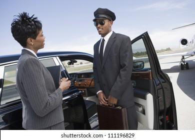 Businesswoman and driver standing by car on airfield
