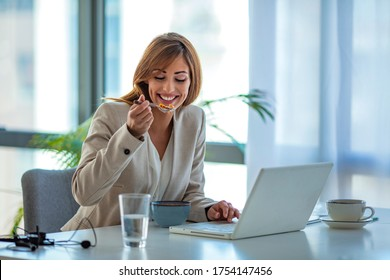 Businesswoman eating cereal and looking at laptop in office. Eat good, work good. Woman has healthy business lunch in modern office interior, diet and vegetarian nutrition concept.