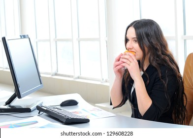 businesswoman eating a doughnut in her office