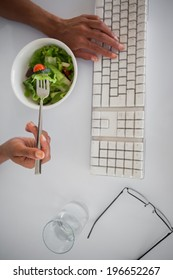 Businesswoman eating a salad at her desk in her office