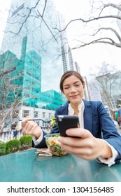 Businesswoman eating salad on lunch break in park. Young professional Asian business woman using phone online data for texting in New York City, USA. Biracial lady Asian Chinese / Caucasian.