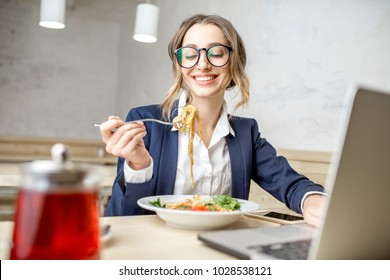 Businesswoman enjoying pasta meal sitting with laptop at the white cafe interior