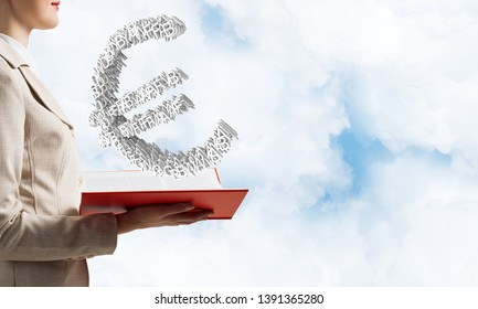 Businesswoman with euro currency sign from letters above opened notebook. Investment and money saving services. Elegant woman in business suit on background of skyscape. Financial company advertising.
