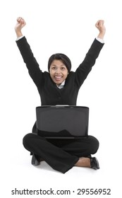 A businesswoman is excited while sitting on the floor with her laptop.