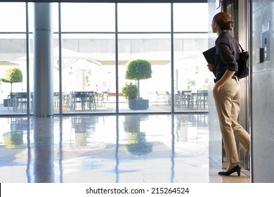 Businesswoman exiting elevator into lobby, carrying shoulder bag and folder, side view