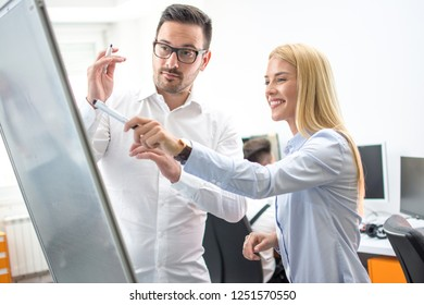 Businesswoman explaining graph to male colleague in office. Office worker giving a presentation on a flipboard in bright office