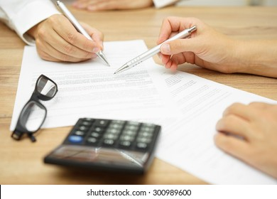 Businesswoman is explaining terms and conditions in agreement to his client before he sign the document