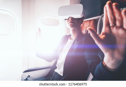 Businesswoman exploring virtual reality for controlling successful business solutions and development of a work plan.Contemporary advanced technology and innovation. Female wear VR gadget in airplane