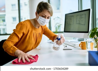 Businesswoman with face mask disinfecting her desk while working in the office during virus epidemic.