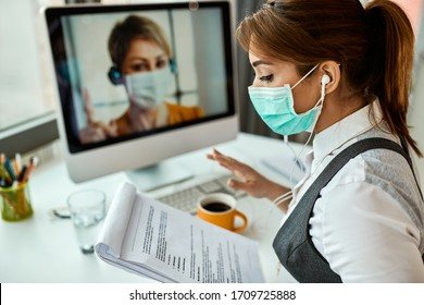 Businesswoman with face mask going through reports while having online meeting with her colleague in the office.