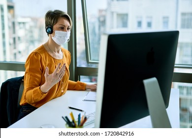 Businesswoman with face mask working on desktop PC and communicating with someone over headset in the office.