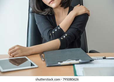 Businesswoman feeling pain in neck shoulder after sitting at desk. Tired woman suffering of office syndrome after long hours work on computer.
