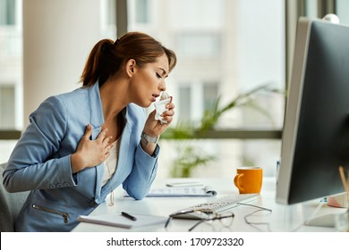 Businesswoman feeling sick and coughing while working on a computer in the office.