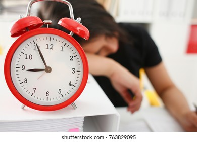 Businesswoman fell asleep in the office connection with processing fatigue. The red alarm clock shows five minutes to nine o'clock morning or evening after the party no strength wake up work normally