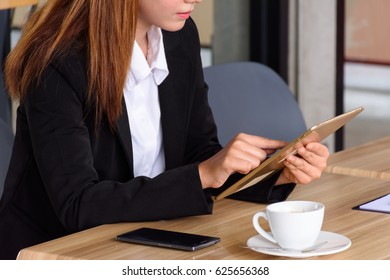 Businesswoman, female employee Playing electronic equipment Drink coffee or tea In a cafe