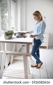 Geschäftsfrau mit ffp2 Maske, die an ergonomischem Stehtisch arbeitet.