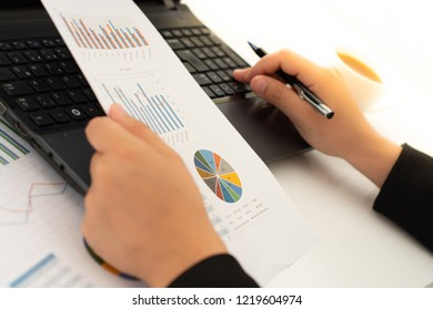 Businesswoman with financial documents using laptop at desk