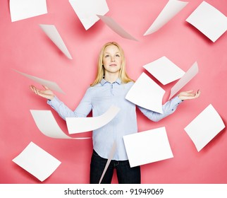 Businesswoman with flying papers on pink background