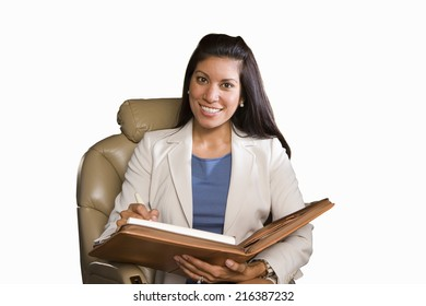 Businesswoman with folder in leather chair, smiling, cut out