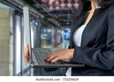 Businesswoman in formalwear using  notebook computer over office background / Business conceptual