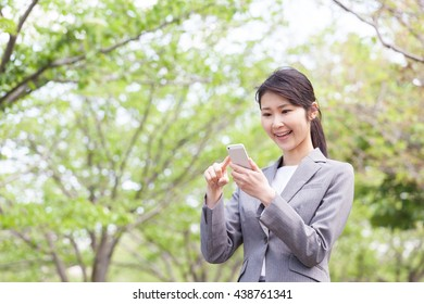 Businesswoman, fresh green to use a smart phone, mobile phone