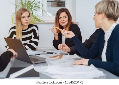 Businesswoman gesturing at a female colleague during a discussion in a team meeting