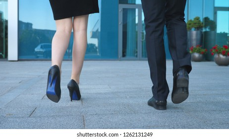 Businesswoman get out from the auto and leaves with her colleague to office. Businessman with his female colleague walking to modern business building. Man and woman commuting to work. Slow motion.