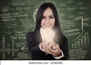 Businesswoman give light bulb in classroom with blackboard background