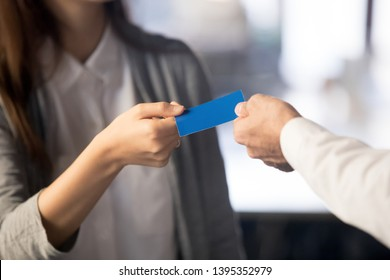 Businesswoman giving business visiting card to businessman, handing contact information about company or individual with address telephone number e-mail and website, close up hands. Contact us concept