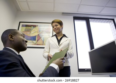 Businesswoman giving file to co-worker