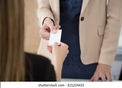 Businesswoman giving her businesscard to her partner. Business meeting, invitation, partnership or hiring concept.