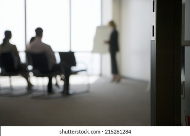 Businesswoman giving presentation to colleagues in conference room, focus on doorway in foreground
