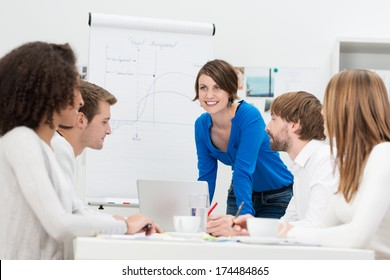 Businesswoman giving a presentation to her team as she stands in front of a flip chart and laptop computer smiling as she answers questions