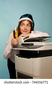 Businesswoman with a glass of champagne standing near photocopier celebrating christmas