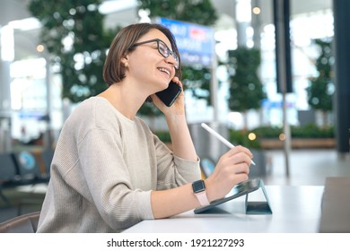 Businesswoman with glasses talks on smartphone and uses digital tablet with pencil. She works, creates new design project or plays mobile games. Modern technologies allow freelancers to work anywhere.