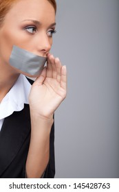 Businesswoman gossiping. Portrait of beautiful young businesswomen with her mouth covered with an adhesive tape standing isolated on gray and  holding her hand near mouth