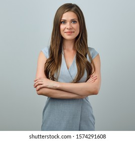 Businesswoman in gray dress studio portrait with arms crossed. Isolated smiling girl on  studio background.