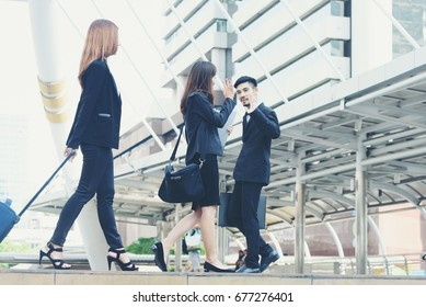 Businesswoman greet each other and waving hand to friend on street
