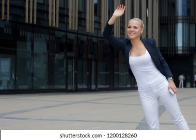 businesswoman greets her colleague, woman is waving her hand