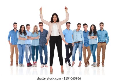 businesswoman group leader celebrating with fingers pointing up and hands in the air while standing on white background, in front of her young casual group