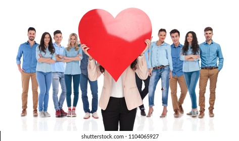 businesswoman group leader holds big red valentine's day heart in front of her casual group while they are standing on white background
