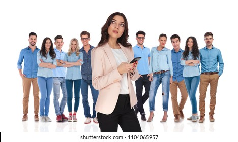 businesswoman group leader with telephone thinking while looking up to side in front of her young casual team, while standing on white background