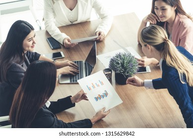 Businesswoman in group meeting discussion with other businesswomen colleagues in modern workplace office with laptop computer and documents on table. People corporate business working team concept.