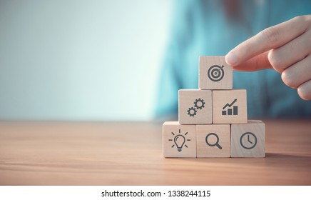 Businesswoman hand arranging wood block with icon business strategy and Action plan, copy space.