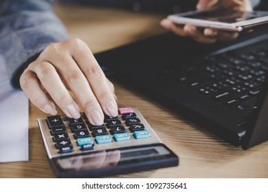 businesswoman hand calculating while working on computer laptop other hand holding smart phone