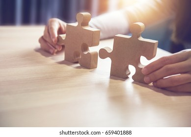 Businesswoman hand connecting jigsaw puzzle on desk, Business solutions, success and strategy concept