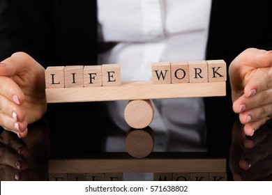 Businesswoman Hand Covering Balance Between Life And Work On Seesaw At Table