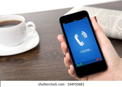 businesswoman hand holding a phone with ringing phone receiver on a screen against the background of a table in the office