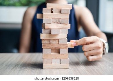 Businesswoman hand placing or pulling wooden block on the tower. Business planning, Risk Management, Solution and strategy Concepts