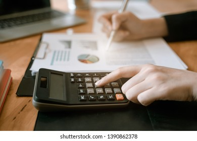 Businesswoman hand pressing on calculator for calculating cost estimating.